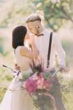 Zakończenie pionowo fotografia uroczy nowożeńcy niesie bicykl z bukietem menchie kwitnie przy Zdjęcie Royalty Free