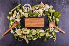 Zakończenie pokrojeni warzywa po środku drewnianej deski i urządzeń na stronach na czarnym tle, zdjęcia royalty free