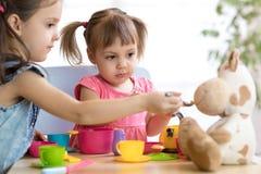 Zakończenie portret śliczny uroczy małych dzieci karmić kracze mokiet zabawka obraz stock