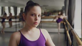 Zakończenie portret ciemnowłosa mała dziewczynka w bodysuit pozyci w balet klasie i patrzeć kamerę Inni ucznie zdjęcie wideo