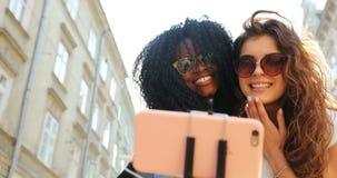 Zakończenie portret dwa pięknej wielokulturowej dziewczyny ściska podczas gdy brać selfies w pogodnej ulicie zbiory