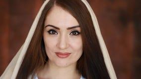 Zakończenie portret dzwoniący hijab młody i tajemniczy arabska kobieta w chustka na głowę, ono uśmiecha się i spojrzenia przy kam zdjęcie wideo