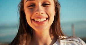 Zakończenie portret młoda atrakcyjna kobieta patrzeje kamerę z dużym pięknym uśmiechem i naturalnym makijażem 4K zdjęcie wideo