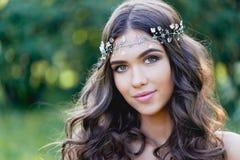 Zakończenie portret młodej brunetki Europejski typ z długim kędzierzawym włosy i dekoracją na, fotografia stock