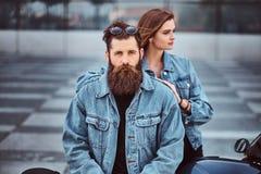 Zakończenie portret modniś para brutalna brodata samiec i jego dziewczyna ubierał w cajg kurtkach przeciw zdjęcie stock