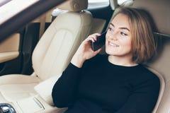 Zakończenie portret piękny szczęśliwy i śmiać się z wszystkie ząb młodą Kaukaską kobietą siedzi w samochodzie i opowiada na mobil Fotografia Stock