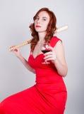 Zakończenie portret pije czerwone wino i trzyma kij bejsbolowego Elegancka młoda rudzielec kobieta w czerwonej sukni, zdjęcia royalty free