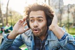 Zakończenie portret z podnieceniem i zafascynowany młody afroamerykanin z afro fryzurą, siedzący w partk i słuchaniu Obrazy Stock