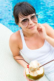 Zakończenie portreta młoda ładna kobieta pije kokosowego koktajl przeciw plenerowemu basenowi Obrazy Stock