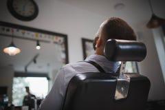 Zakończenie przystojny mężczyzna obsiadanie w fryzjera ` s krześle Młoda elegancka samiec z brodą w zakładzie fryzjerskim zdjęcia stock