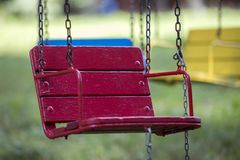 Zakończenie pusty drewniany błękit, kolor żółty, rocznika barwiący carousel obwieszenie na łańcuchach siedzenia fotografia stock