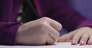 Zakończenie ręka dziewczyna remis na białym papierze przy stołem troszkę zbiory wideo