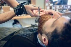 Zakończenie ręka fryzjer męski używa nożyce podczas gdy żyłujący t Obraz Royalty Free