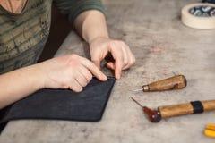 Zakończenie ręka garbarz up wykonuje pracę na stole z narzędziami Zdjęcia Royalty Free