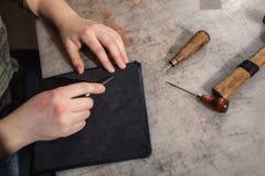 Zakończenie ręka garbarz up wykonuje pracę na stole z narzędziami Zdjęcie Royalty Free