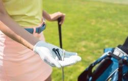 Zakończenie ręka kobieta trzyma trzy trójnika na polu golfowym Obraz Royalty Free
