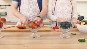 Zakończenie ręka mężczyzna i kobieta który przygotowywają owocowej sałatki z truskawkami zdjęcie wideo