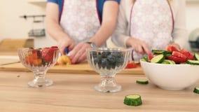 Zakończenie ręka mężczyzna i kobieta który przygotowywają owocowej sałatki z truskawkami zbiory