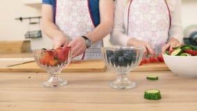 Zakończenie ręka mężczyzna i kobieta który przygotowywają owocowej sałatki z truskawkami zbiory wideo