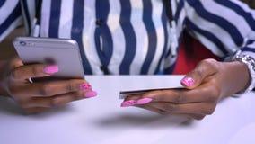 Zakończenie ręki afrykańskiej kobiety pisać na maszynie numer karty kredytowej na telefonie podczas gdy siedzący
