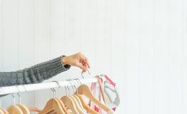 Zakończenie ręki kobiety up wybierać odziewa w przebieralni fotografia stock