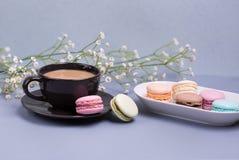 Zakończenie ranku czerni filiżanka kawy z mlekiem, tortowym macaron i kwiatem na błękita stole, piękny deser fotografia stock