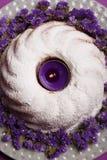 Zakończenie ringowy tort na talerzu z małymi kwiatami i zaświecającą świeczką na jaskrawym fiołkowym tle, dekorujący Zdjęcie Stock
