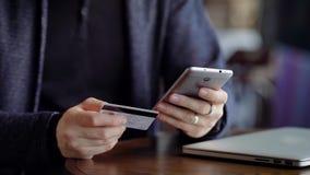 Zakończenie samiec up wręcza pisać na maszynie w smartphone klingerytu numer karty Młody człowiek w cukiernianym płaci rachunku z zbiory wideo