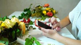 Zakończenie smartphone i ręki żeńska kwiaciarnia która jedzie palce przez ekran gadżet wśród kwiecistego układamy zbiory