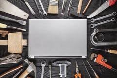 Zakończenie srebny laptop z narzędziami na czarny drewnianym Fotografia Stock