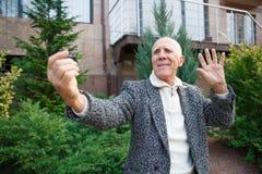 Zakończenie starszy mężczyzna macha jego w szarej kurtce z szarymi brwiami na mini kamerze ręka obraz royalty free