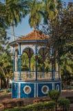 Zakończenie stary kolorowy gazebo po środku zielenisty ogrodowy pełnego drzewa, w słonecznym dniu przy São Manuel obraz stock