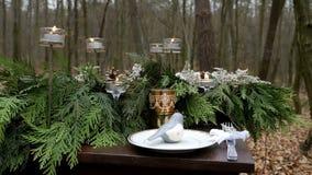 Zakończenie strzał drewniany stół dekorujący z świerczyn gałąź, płonącymi świeczkami, szkłem i naczyniem, las jesieni zbiory