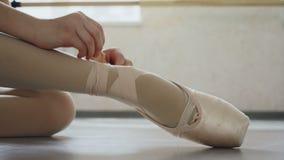 Zakończenie strzał małej dziewczynki ` s stopa w pointe bucie rękach i stawia na fachowym obuwiu i wiąże faborek wokoło zbiory wideo