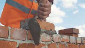 Zakończenie strzał murarz stawia cegłę na ścianie zdjęcie wideo
