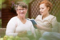 Zakończenie szczęśliwa starsza kobieta nu i jej młody profesjonalista obrazy stock