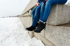 Zakończenie szczęśliwej i kochającej pary podróżnika nożny obsiadanie na granitowym nabrzeżu Para w zima butach i ciepłych pulowe obraz royalty free
