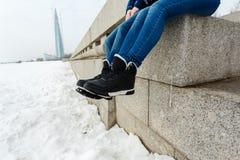 Zakończenie szczęśliwej i kochającej pary podróżnika nożny obsiadanie na granitowym nabrzeżu Para w zima butach i ciepłych pulowe obraz stock