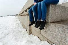 Zakończenie szczęśliwej i kochającej pary podróżnika nożny obsiadanie na granitowym nabrzeżu Para w zima butach i ciepłych pulowe zdjęcia stock