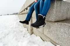 Zakończenie szczęśliwej i kochającej pary podróżnika nożny obsiadanie na granitowym nabrzeżu Para w zima butach i ciepłych pulowe zdjęcie royalty free