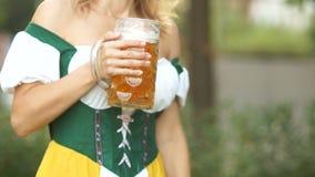 Zakończenie szkło Bawarski piwo w rękach młoda kelnerka ubierał w obywatelu odziewa Festiwale muzyka zbiory wideo