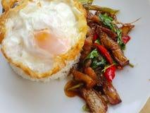 Zakończenie, Tajlandzki jedzenie: smażący basil z crispy wieprzowiny jajkiem Zdjęcie Royalty Free