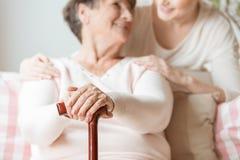 Zakończenie trzyma chodzącego kij w pielęgnaci h starsza kobieta obrazy royalty free