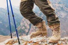 Zakończenie turystyczna ` s stopa w trekking inicjuje z kijami dla Północnej chodzącej pozyci na kołysa kamień w górach Obraz Royalty Free