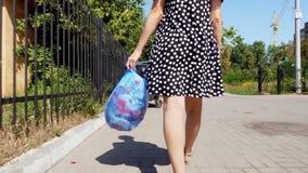 Zakończenie, tylny widok, dziewczyna niesie pakunek śmieci w jej rękach, rzuca out grat Lato gorący dzień ekologia zdjęcie wideo