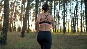 Zakończenie uśmiechnięta kobieta up wkłada hełmofony i bieg w ucho przez jesień lasu przy zmierzchem swobodny ruch zdjęcie wideo