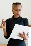 Zakończenie ufna elegancka biznesowa kobieta jest ubranym czerni suknię w lekkim biurze sprawdza jej agendę Fotografia Royalty Free