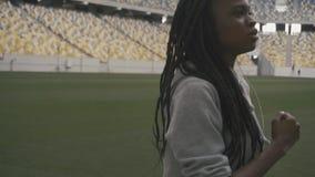 Zakończenie ufnej amerykanin afrykańskiego pochodzenia nastoletniej dziewczyny słuchająca muzyka i jogging na miastowym stadium t zbiory