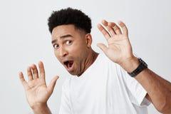 Zakończenie up śmieszny atrakcyjny ciemnoskóry afrykański męski uczeń z kędzierzawym włosy w przypadkowych białych koszulki podes obrazy stock