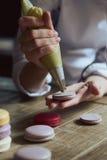 Zakończenie up żeńska ciasto szefa kuchni ręka gotuje wyśmienicie macaroon Fotografia Stock